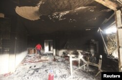 FILE - A man walks inside the U.S. consulate in Benghazi, which was attacked September 11 and set on fire by al-Qaida gunmen, Sept. 12, 2012.