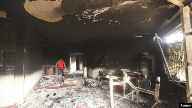 A man walks inside the U.S. consulate in Benghazi, which was attacked September 11 and set on fire by al-Qaida gunmen who killed Christopher Stevens, the U.S. ambassador to Libya, and three embassy staff, in Libya, September 12, 2012.