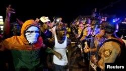 Para pengunjuk rasa meneriakkan protes ke arah barisan polisi sebelum terjadinya penembakan di Ferguson, Missouri (9/8).