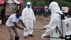 Nhân viên y tế sát khuẩn sau khi lấy mẫu máu kiểm tra ở khu vực mà cậu bé 17 tuổi đã chết vì Ebola tại Liberia hôm 30/6/2015.