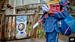 USPS carrier Jamesa Euler encounters barking dog in the Cabbagetown neighborhood of Atlanta, Ga., Feb. 7, 2013.