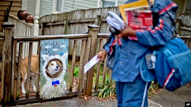 USPS carrier Jamesa Euler encounters barking dog in the Cabbagetown neighborhood of Atlanta, Ga., Feb. 7, 2013.