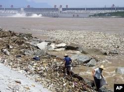 2010年8月,工人在三峡大坝附近清理洪水带来的垃圾