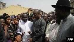 Tổng thống Nigeria Goodluck Jonathan (phải) nói chuyện với gia đình các nạn nhân vụ đánh bom nhà thờ đêm Giáng sinh tại Nhà thờ Thánh Theresa ở Madalla, ngày 31/12/2011