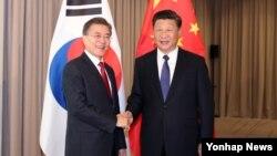 문재인 한국 대통령과 시진핑 중국 국가주석이 6일 베를린 인터콘티넨탈 호텔에서 열린 한-중 정상회담에서 악수하며 미소 짓고 있다.