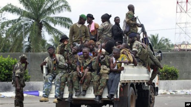 Soldiers loyal to Alassane Ouattara, along with several men who were detained for unknown reasons, drive past a checkpoint serving as an operating base, at one of the main entrances to Abidjan, Ivory Coast, April 7, 2011.