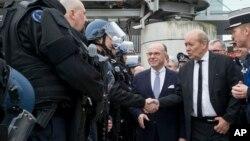 Le ministre français de la Défense Jean-Yves Le Drian, au centre, et le son homologue de l'Intérieur Bernard Cazeneuve, 2e à droite, saluent des policiers français lors d'une inspection des mesures de sécurité à l'aéroport Charles de Gaulle, à Roissy, au nord de Paris, 23 mars 2016.