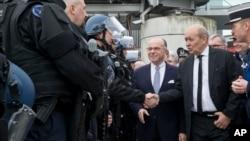 法國內政部長伯納德卡澤納夫(中)巡示機場與警衛人員。