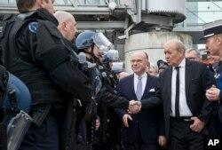 Bộ trưởng Nội vụ Pháp Bernard Cazeneuve (thứ 2-bên phải) và Bộ trưởng Quốc phòng Jean-Yves Le Drian bắt tay các sĩ quan cảnh sát Pháp khi họ kiểm tra các biện pháp an ninh tại sân bay Charles de Gaulle ở Roissy, phía bắc Paris, ngày 23 tháng 3 năm 2016.