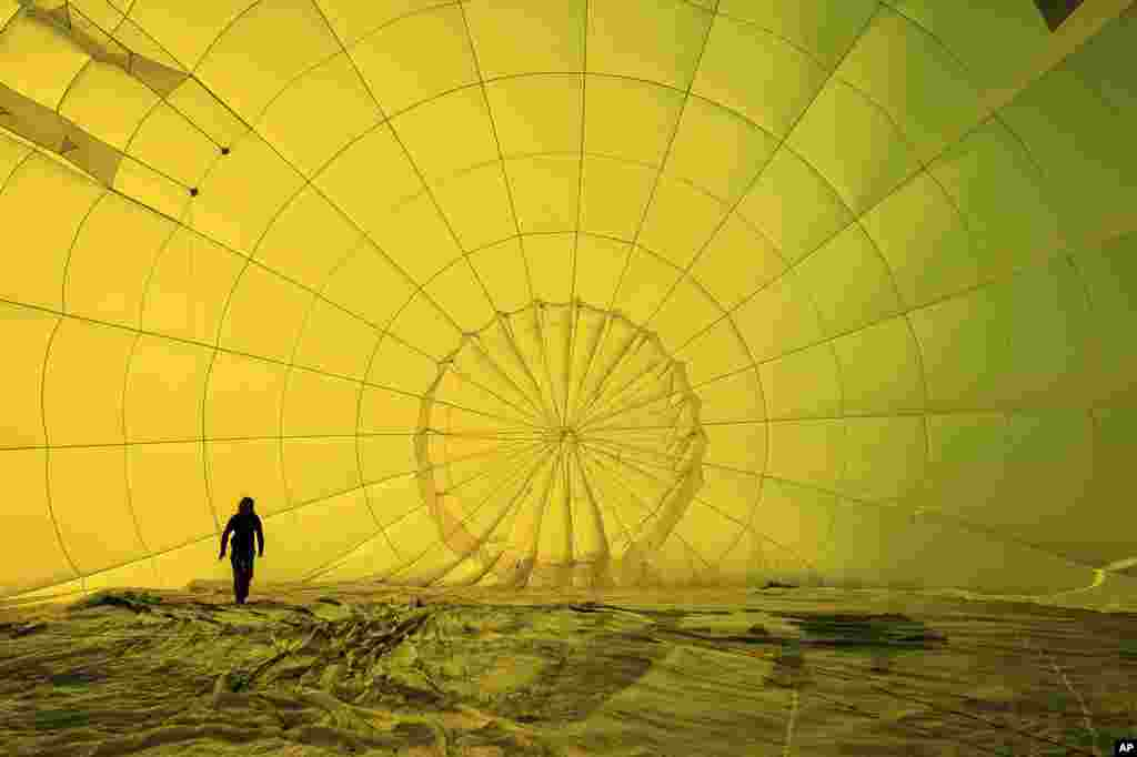 A hot air balloon pilot checks her rigging inside the canopy before a mass ascent, with 43 balloon teams taking part, for a Fiesta Flypast over the city of Bristol, UK, as part of the socially distanced alternative to the Bristol International Balloon Fiesta.