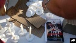 Una biblia y velas colocadas por voluntarios durante una vigilia por las víctimas del tiroteo en la escuela secundaria Marjory Stoneman Douglas, el jueves 15 de febrero de 2018.