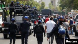 Polisi berjaga di kawasan pasar ikan La Viga di Mexico City, Meksiko, yang ramai di tengah pandemi Covid-19, 9 April 2020. (Foto: dok).
