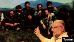Iranian controversial conservative activist Saeed Ghasemi during an Interview with a photo in background showing him and his comrades during the Bosnian conflict in the early 1990s.