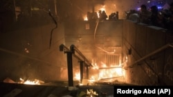 Protesters burn a subway station in Santiago, Chile, Monday, Oct. 28, 2019.
