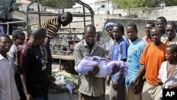 Somali man carries body of one-year-old child who was killed by errant al Shabab mortar targeting presidential palace, Mogadishu, March 19, 2012.