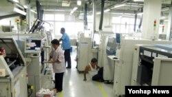 27일 개성공단 입주기업인 BK전자의 북측 근로자들이 공장 재가동을 위해 기계 설비 보수작업 및 청소 작업을 하고 있다.