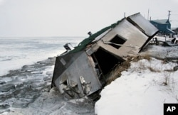 FILE - In this Dec. 8, 2006, file photo, Nathan Weyiouanna's abandoned house at the west end of Shishmaref, Alaska, sits on the beach after sliding off during a fall storm in 2005. Unofficial ballot returns from a special election held on Tuesday, Aug. 16