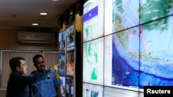 Indonesia's vice-president Jusuf Kalla (L) monitors progress in the search for AirAsia Flight QZ8501 during a visit to the National Search and Rescue Agency in Jakarta, December 28, 2014.