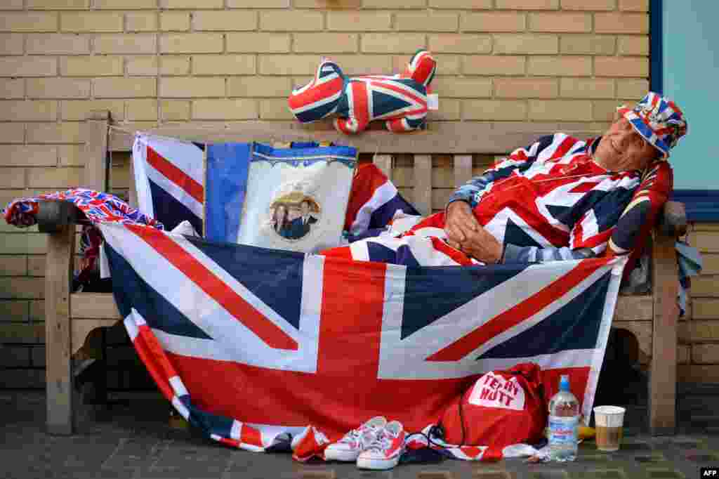 Royal supporter Terry Hutt poses for pictures on a bench where he has been camped out for nine days outside the Lindo Wing of St Mary's Hospital in London, where Prince William and his wife Catherine's baby is expected to be born.