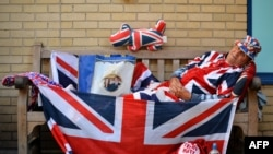 Royal supporter Terry Hutt poses for pictures on a bench where he has been camped out for 12 days outside the Lindo Wing of St Mary's Hospital in London, where Prince William and his wife Catherine's baby is expected to be born.