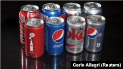 FILE PHOTO: Regular and mini cans of Coke and Pepsi are pictured in this photo illustration in New York, August 5, 2014. REUTERS/Carlo Allegro/File Photo