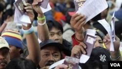 Miles de filipinos evacuados de Libia arribaron a Manila y muestran sus pasaportes para poder ingresar al país.