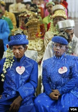Indonesian couples wait for their turn to wed during a mass wedding ceremony in Jakarta, Indonesia, Wednesday, May 18, 2005. The mass marriage of the 47 couples was held by the State Secretariate to help the poor who were unable to afford proper wedding. (AP Photo/Dita Alangkara)