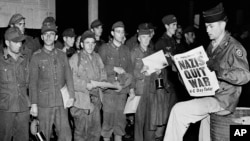 Pfc. Clarence K. Ayers of Evansville, Ind., reads the news of VE Day as newly arrived German prisoners stand of a New York City pier on May 8, 1945.