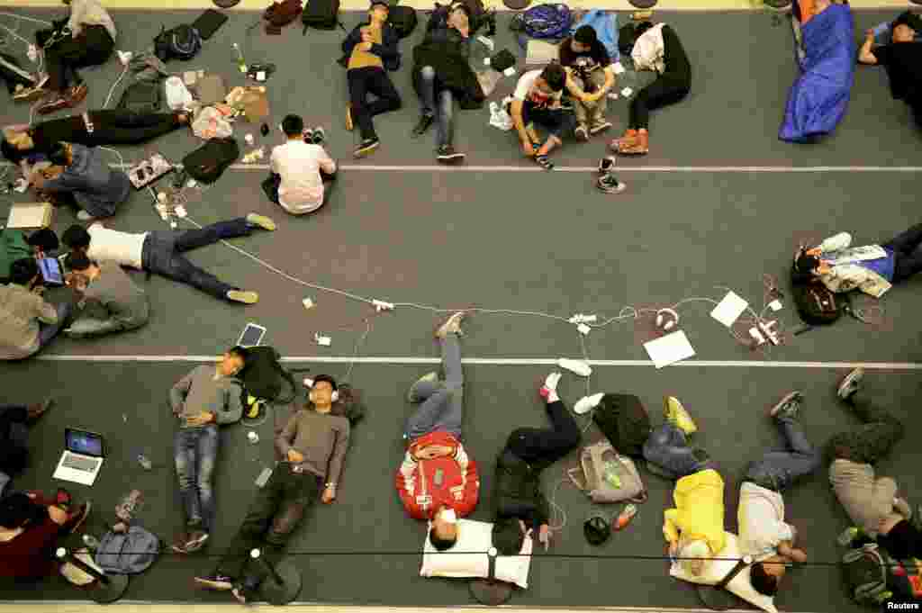 People sleep on the floor as they line up for the opening of a new Apple Store in Hangzhou, Zhejiang province, China. The 19th Apple Store in mainland China and second one in the city opened on Friday.