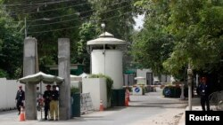 FILE - A policeman (2nd R) and private security personnel stand guard at the entrance of a road leading towards the U.S. consulate in Lahore.