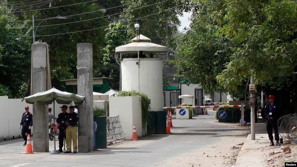 Офицер полиции и сотрудники частной охранной фирмы охраняют въезд на КПП на дороге, ведущей к консульству США в Лахоре, Пакистан (архивное фото)