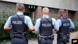 FILE - German police officers guard outside the regional court in Frankfurt, Germany, Monday, Sept.15, 2014.
