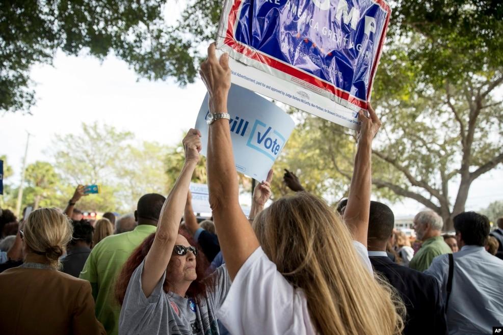 两派标语对峙。希拉里·克林顿在一个提前投票地点外欢迎支持者的时候,一名克林顿的支持者试图挡住一名川普支持者举起的标语牌