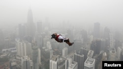 A BASE jumper leaps from the 300-metre high Kuala Lumpur Tower during the International Tower Jump in which more than 100 people take part, on a hazy day in Kuala Lumpur, Malaysia, Oct. 2, 2015.