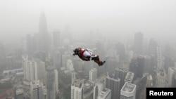Seseorang melakukan aksi melompat dari ketinggian 300 meter dari Kuala Lumpur Tower di tengah hari berkabut asap di kota itu (2/10). (Reuters/Olivia Harris)