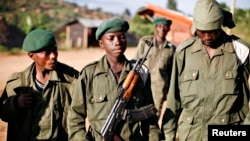 "A child soldier (C), known as ""Kadogo,"" meaning ""small one"" in Swahili, stands at the front line at Kanyabayonga in eastern Congo, November 17, 2008. Snatched from their homes by armed men who force them to carry ammunition, fight and kill, beaten if they"