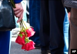 In this grab taken from footage by the Russian State Atomic Energy Corporation ROSATOM press service, a woman holds roses as people gather for the funerals of five Russian nuclear engineers killed by a rocket explosion in Sarov, Aug. 12, 2019.