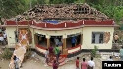 Warga berkumpul di sekitar kuil yang hancur setelah insiden kebakaran di Kollam negara bagian Kerala, India (10/4).