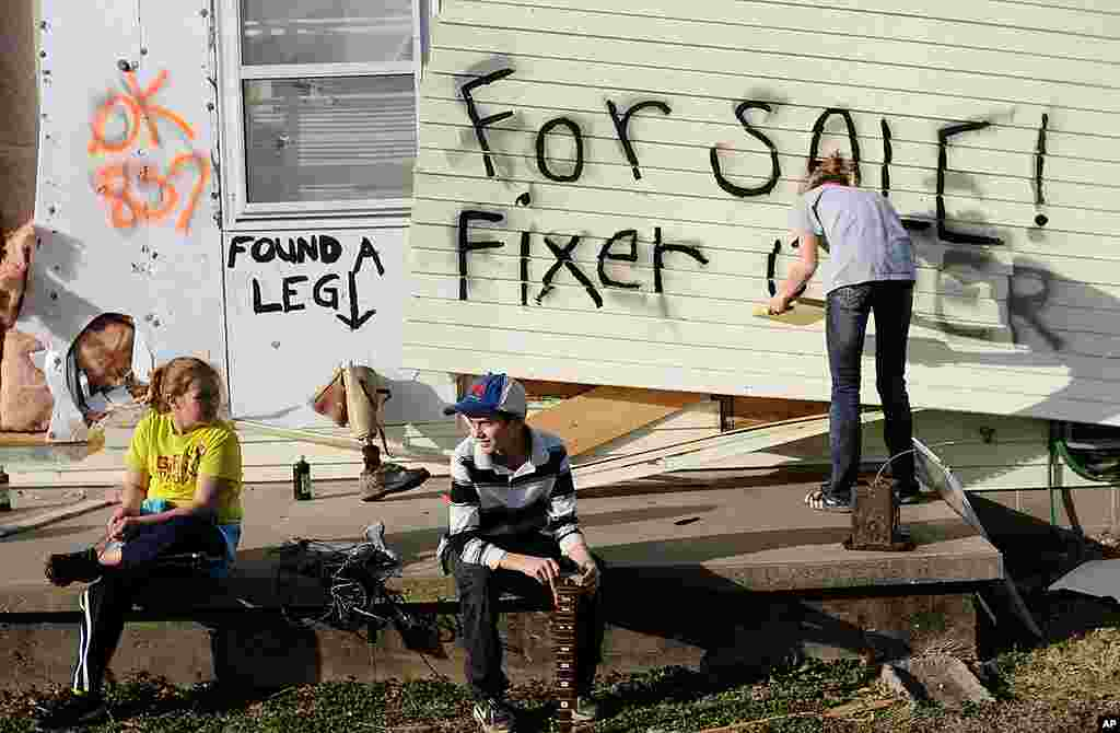 "Children sit on the front porch as Lindsey Murray, 15, of Harrisburg, Illinois paints ""for sale fixer upper"" on the side of the home of their grandmother that was destroyed in a tornado. February 29, 2012. (AP)"