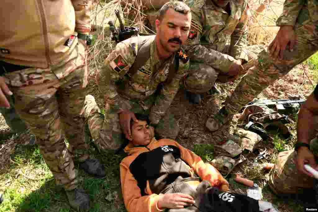 کمک سربازان عراقی به پسری که در نبرد بین داعش و ارتش عراق مجروح شده است. موصل، عراق.