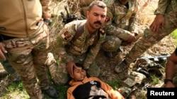 REUTERS Força de Intervenção Rápida iraquiana ajuda um rapaz ferido após ataque em Mosul, 24 Fev.