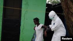 Wani ma'aikacin kiwon lafiya yake kawo wata mace da ake tuhuma ta kamu d a cutar Ebola