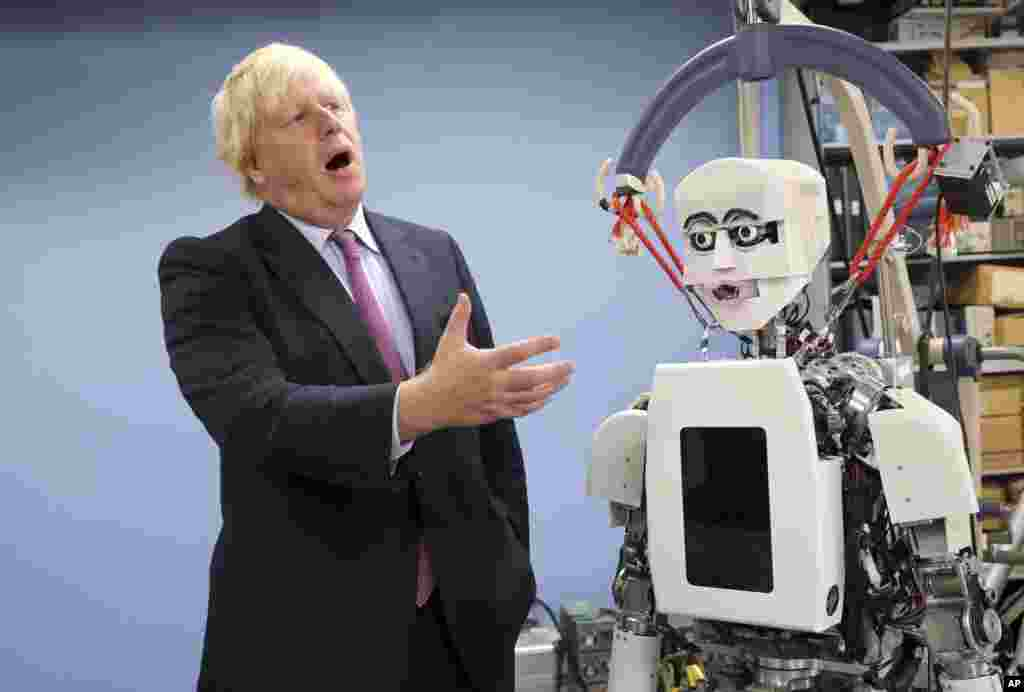 Britain's Foreign Secretary Boris Johnson gestures as he looks at a humanoid robot at Research Institute for Science and Engineering at Waseda University's campus in Tokyo.