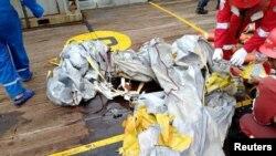 Pekerja PT Pertamina Persero di kapal Prabu milik Pertamina, memeriksa barang-barang yang diyakini dari pesawat Lion Air JT610 yang jatuh, di lepas pantai Kabupaten Karawang, Jawa Barat, 29 Oktober 2018. (Foto: Antara/PT Pertamina via Reuters)