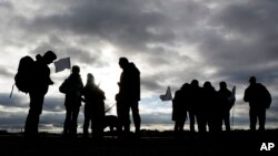 Demonstrators with white flags silhouette against a cloudy sky as they wait for the launch of the Civil March for Aleppo at Tempelhof former airport in Berlin, Dec. 26, 2016.