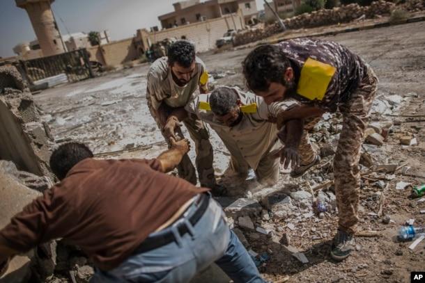 리비아 시르테에서 정부에 충성하는 무장대원들이 저격수의 총에 맞은 다른 대원을 구출하고 있다.