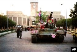 FILE - Tanks manned by Taliban fighters and decorated with flowers are seen in front of the the damaged Presidential palace in Kabul, Afghanistan, Sept. 28, 1996.