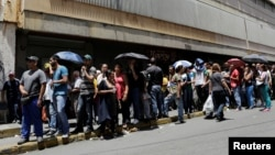 FILE - People queue up to try to buy basic food items outside a supermarket in Caracas, Venezuela, April 28, 2016.