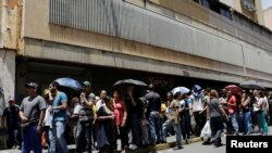 Rakyat Venezuela antri untuk membeli bahan dasar pangan di luar supermarket. Caracas, Venezuela