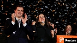 Catalan Ciudadanos leader Ines Arrimadas, center, smiles next to Ciudadanos national leader Albert Rivera at a Ciudadanos rally after results were announced in Catalonia's regional elections in Barcelona, Spain, Dec. 21, 2017.